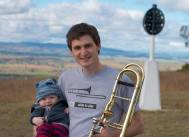 "Nic Gowans from Bathurst, NSW: ""Although I don't have much time for practice since Theodore came along, trombone and music provide an escape from my everyday world of Geodesy. I initially chose trombone because of 'that' sound, but continue with it in several ensembles (Central West Trombone Choir, Bathurst RSL Concert Band & PremiAir V8s) to perform with some excellent musicians and to 'give back' to the community - whether it's playing at ANZAC services, nursing homes or for primary school children. With a trombone as one's instrument of choice the rewards are truly immeasurable."""